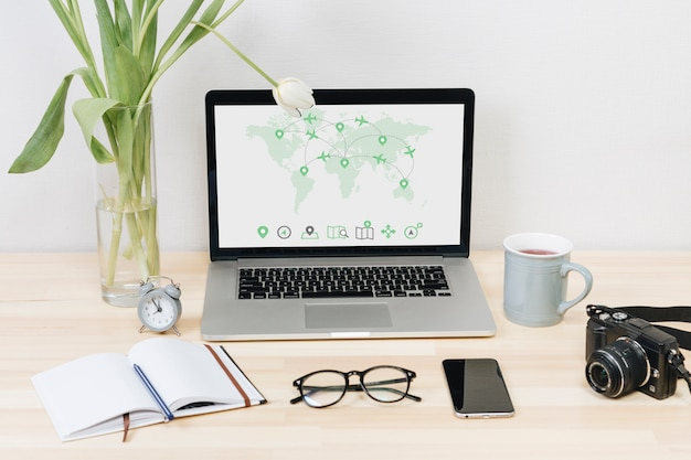 テーブルの上の画面上の世界地図とノートパソコン 無料写真