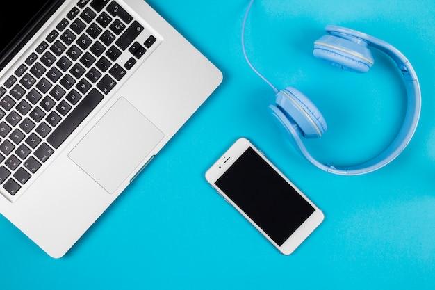 スマートフォンとヘッドフォン付きのラップトップ 無料写真