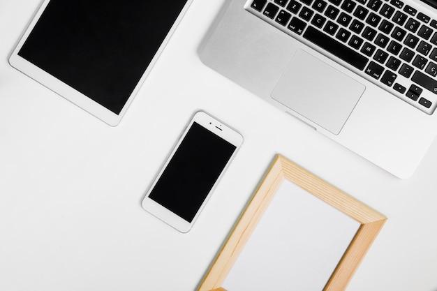 スマートフォンと空白のフレームを持つノートパソコン 無料写真
