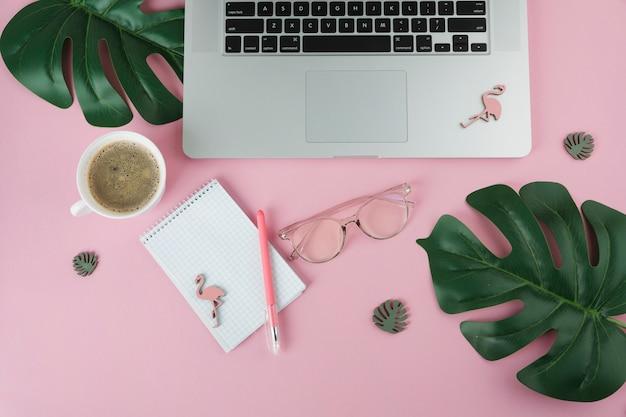 ノートパソコンとテーブルの上の小さなフラミンゴのラップトップ 無料写真