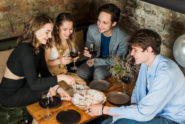 Улыбающиеся пары наслаждаются вечеринкой с пиццей и вином Бесплатные Фотографии