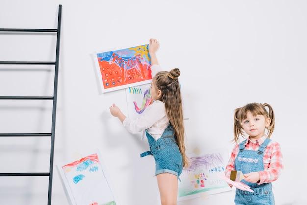 壁に絵をぶら下げ小さな女の子 無料写真