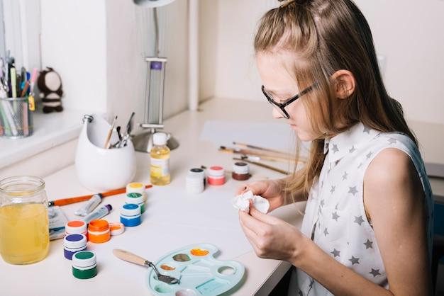ガッシュ缶とパレットのテーブルに座っている女の子 無料写真