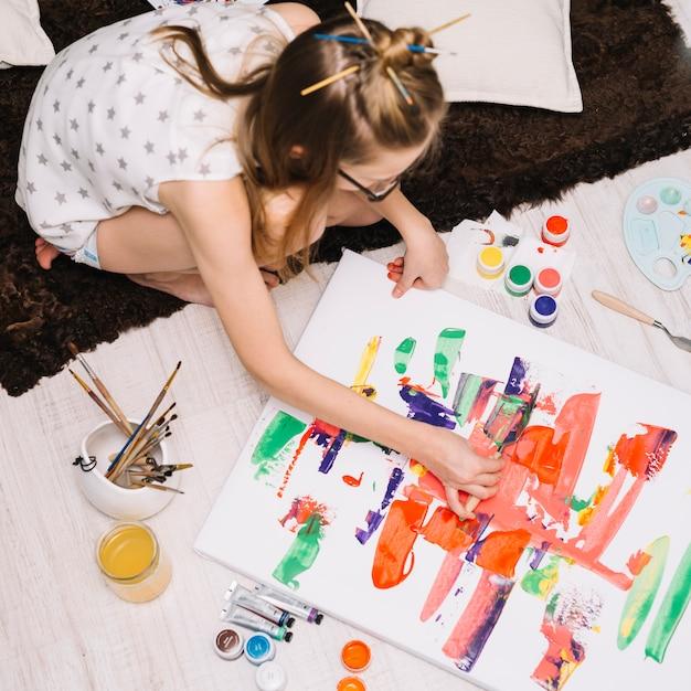 床の上の紙の上の明るいガッシュと絵画の女の子 無料写真