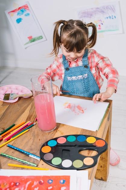 テーブルで紙の上のアクワレルと絵画かわいい女の子 無料写真