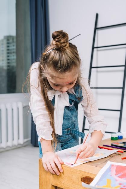 テーブルで紙のシート上にアクワレルと絵画かわいい女の子 無料写真