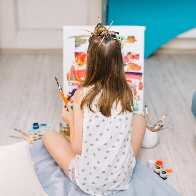 白い床に座ってガッシュで絵の少女 無料写真
