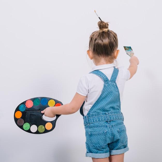 ブラシで小さな女の子の絵の壁 無料写真