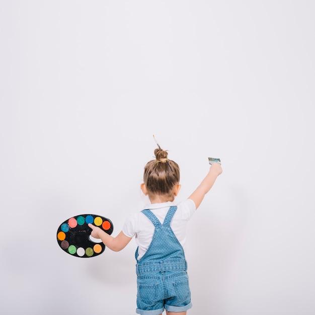 Маленькая девочка красит белую стену кистью Бесплатные Фотографии
