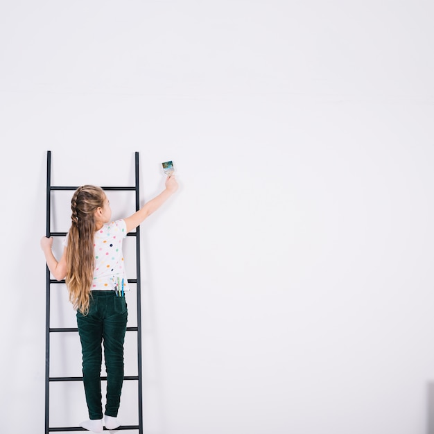 はしごの絵画の壁の少女 無料写真