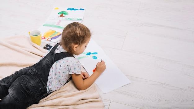 Девушка рисует акварелью на бумаге и лежит на полу Бесплатные Фотографии