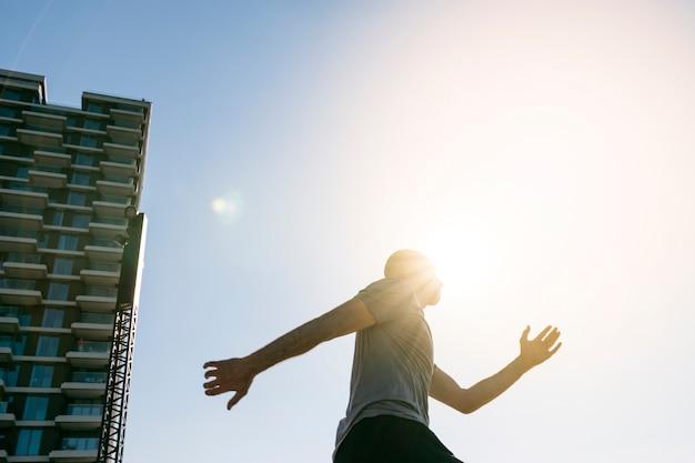 青い空を背景に走っている男性ランナーの上に落ちる日光 無料写真