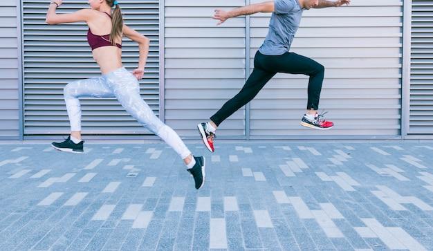 カップル陽気なカップルを実行していると空気中のジャンプ 無料写真