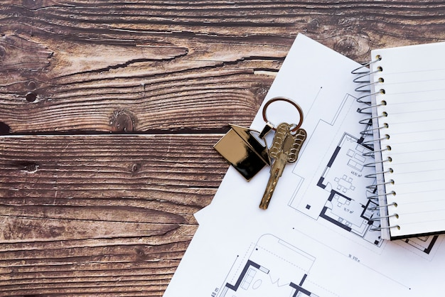 新しい家の青写真と木のテクスチャ背景のスパイラルノートの家の鍵のクローズアップ 無料写真