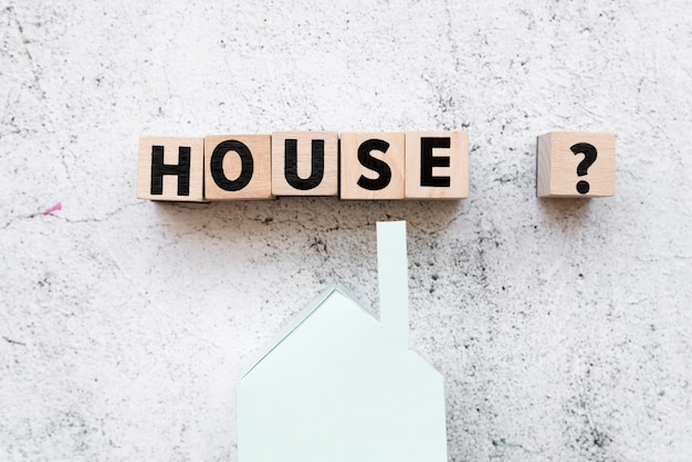 Организованные блоки текста дома со знаком вопроса над моделью бумажного дома на конкретном фоне Бесплатные Фотографии