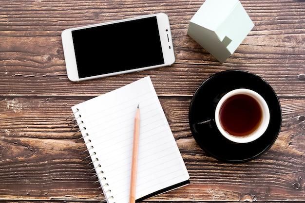 Мобильный телефон; пустой спиральный блокнот; карандаш; кофейная чашка и модель дома на деревянном столе Бесплатные Фотографии