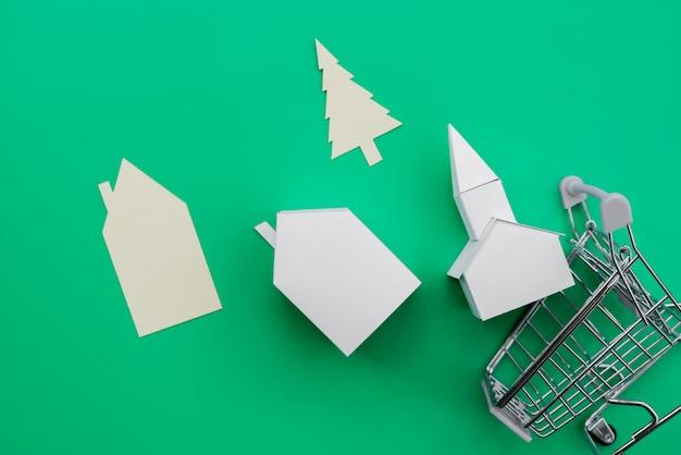 紙の家の種類が異なります。緑の背景の上のショッピングトロリーから落ちてくる木 無料写真