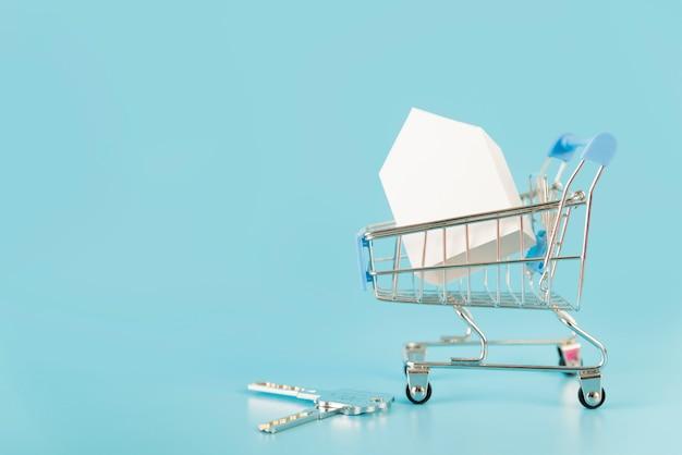 青い背景のキーを持つショッピングカート内のホワイトペーパーの家モデル 無料写真