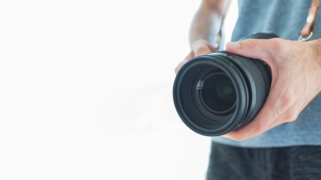 白い背景の上のデジタル一眼レフカメラを持って写真家のクローズアップ 無料写真