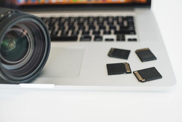 カメラのレンズとラップトップ上のメモリカードのクローズアップ 無料写真