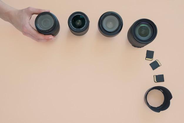 カメラのレンズを配置する人の手のオーバーヘッドビュー。色付きの背景上のメモリカードと拡張リング 無料写真