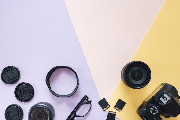 カメラのアクセサリーと色付きの背景上の眼鏡を持つ近代的なデジタル一眼レフカメラ 無料写真