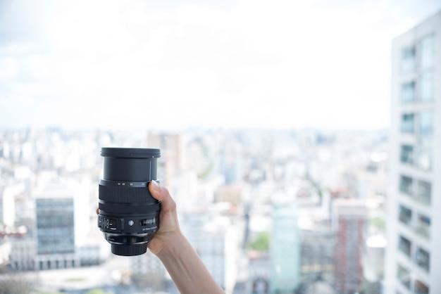ぼやけている建物の背景の前にカメラのレンズを持っている人の手 無料写真