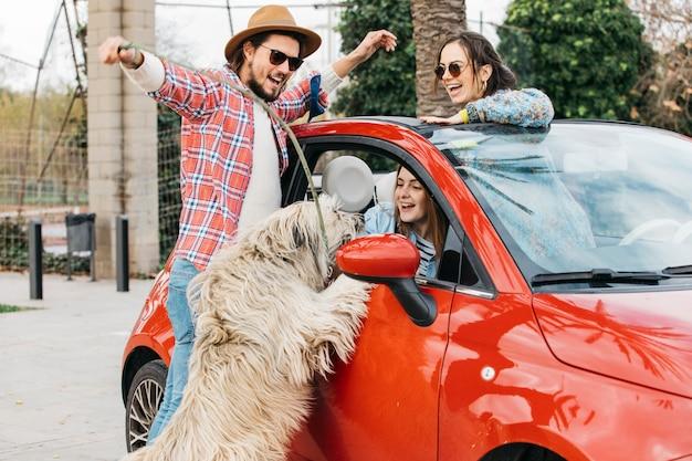 車の近くの大きな犬と一緒に立っている人 無料写真