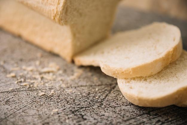 グレーのテーブルに白パンのパンをカットします。 無料写真