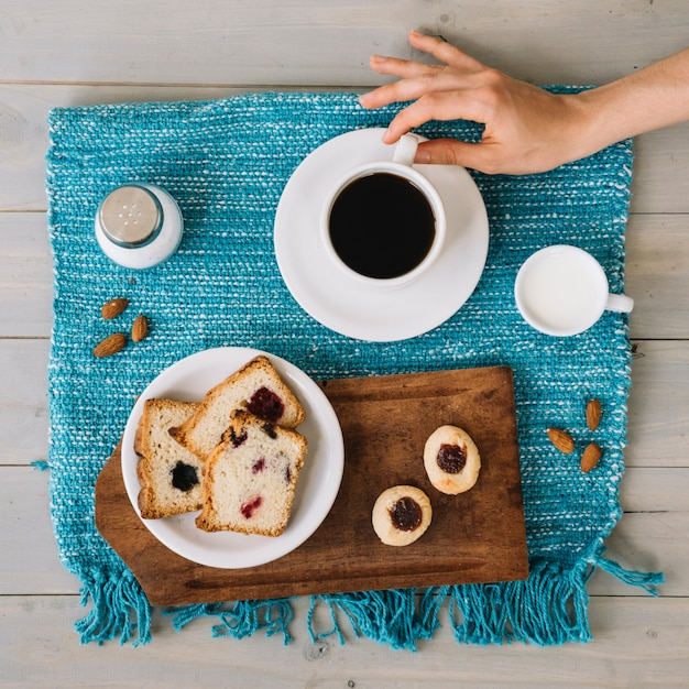 パイとプレートの近くのコーヒーカップを持っている手 無料写真