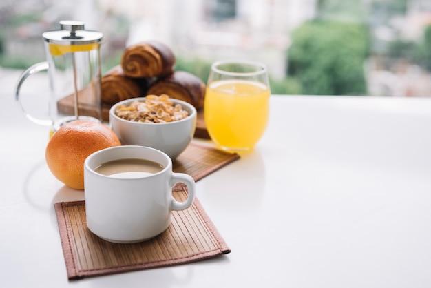 テーブルの上のコーヒーカップとコーンフレーク 無料写真