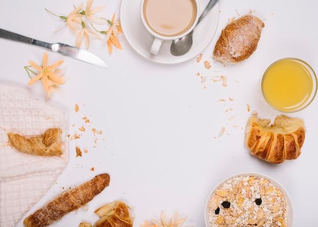 クロワッサンとテーブルの上のコーヒーカップとオートミール 無料写真