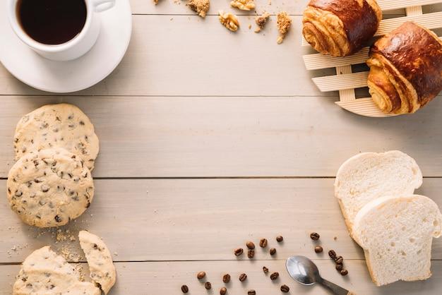 パンとクッキーと木製のテーブルの上のコーヒーカップ 無料写真