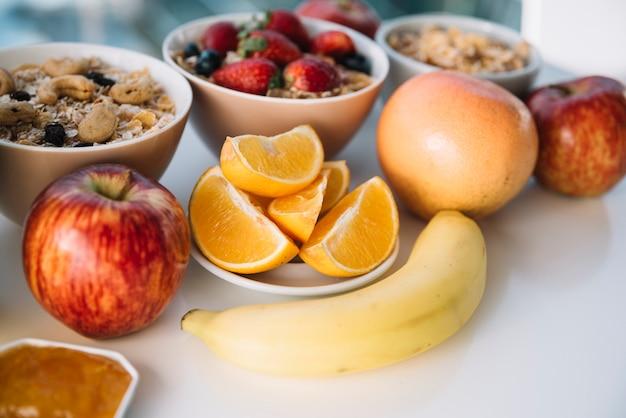 Овсяная каша с фруктами и ягодами на белом столе Бесплатные Фотографии