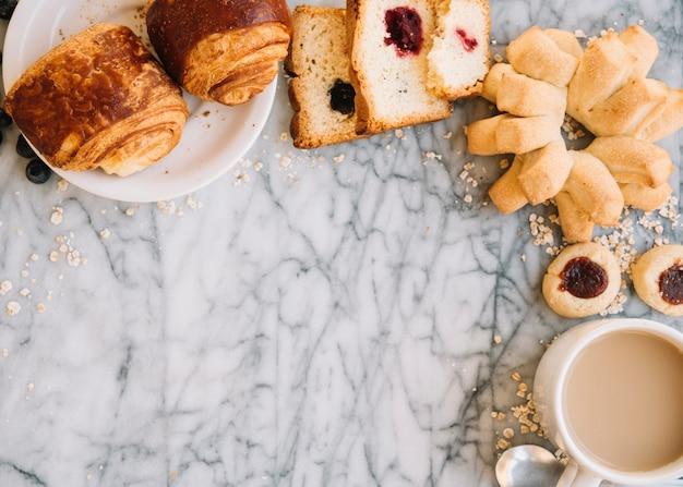 大理石のテーブルの上のパン屋さんとコーヒーカップ 無料写真