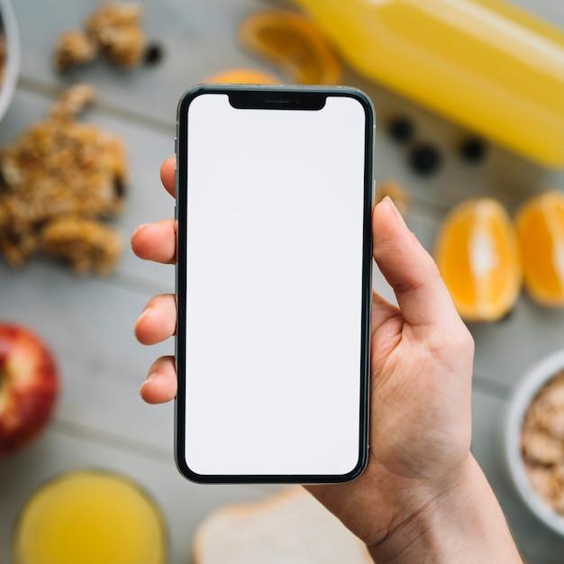 果物の上の空白の画面を持つスマートフォンを持っている人 無料写真