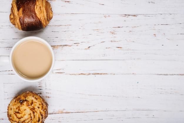 木製のテーブルの上の甘いパンとコーヒーカップ 無料写真