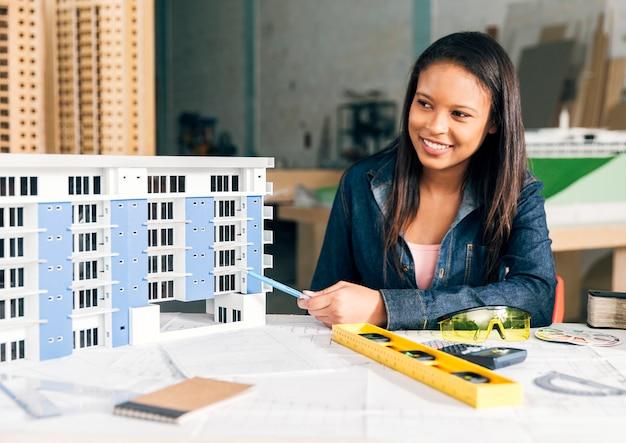 建物のモデルを示すアフリカ系アメリカ人女性の笑みを浮かべてください。 無料写真