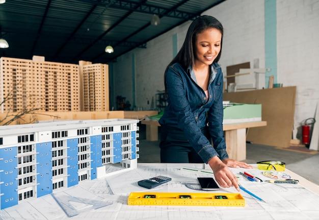 テーブルの上の建物のモデルの近くに立っている陽気なアフリカ系アメリカ人女性 無料写真