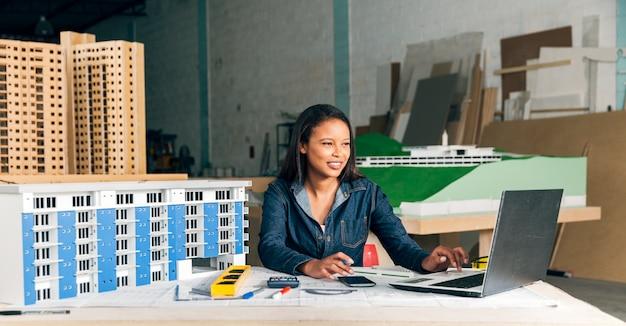 ラップトップと建物のモデルを持つアフリカ系アメリカ人女性の笑みを浮かべてください。 無料写真