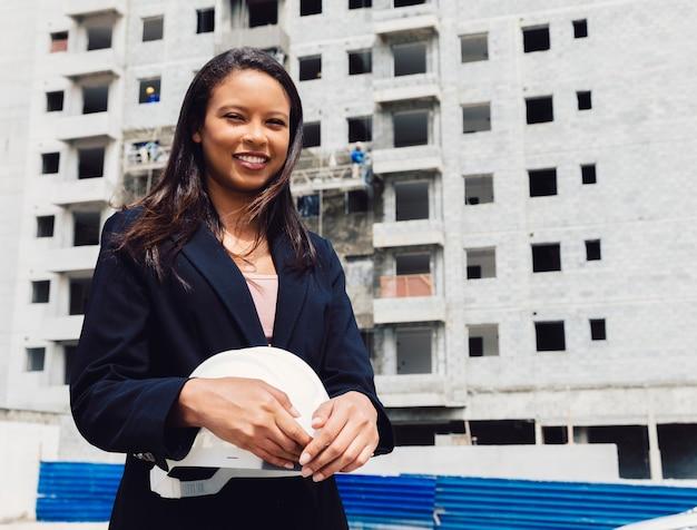 建設中の建物の近くの安全ヘルメットを保持している笑顔のアフリカ系アメリカ人女性 無料写真
