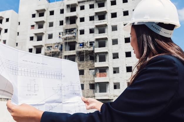 建設中の建物の近くの紙の計画と安全ヘルメットのアフリカ系アメリカ人女性 無料写真