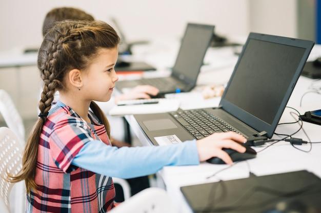 教室でラップトップを使用してかわいい女の子 無料写真