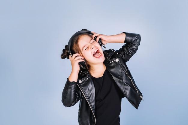 青い背景に対して笑ってヘッドフォンで音楽を聴く少女の肖像画 無料写真