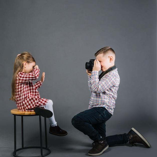 カメラ付きのスツールに座っている女の子の写真を撮る男の子の側面図 無料写真
