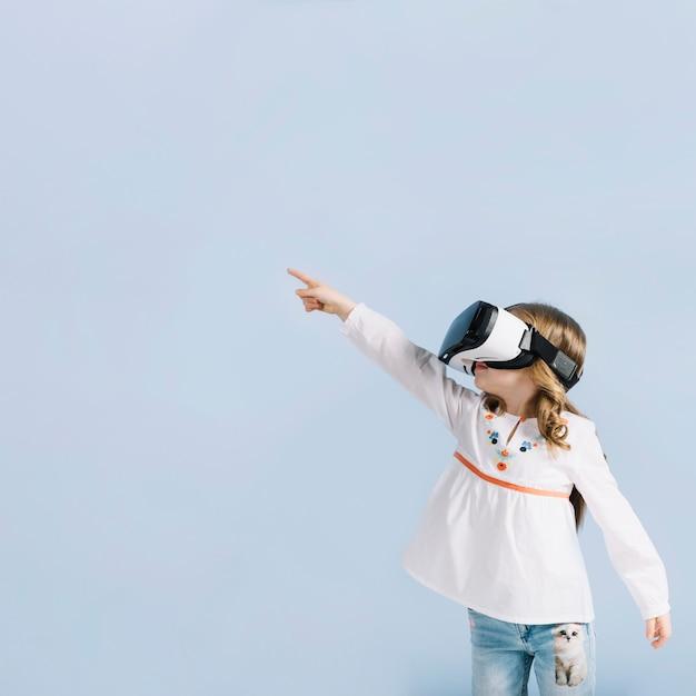 青い背景に対して彼女の指を指しているバーチャルリアリティヘッドセットを着ている少女のクローズアップ 無料写真