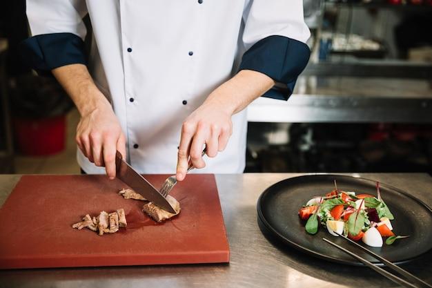 サラダ近くボード上のカットロースト肉を調理します。 無料写真