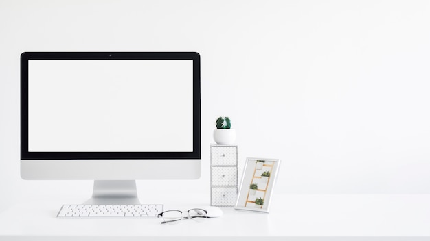 モニター、フォトフレーム、サボテンとテーブルの上の眼鏡の近くのキーボード 無料写真