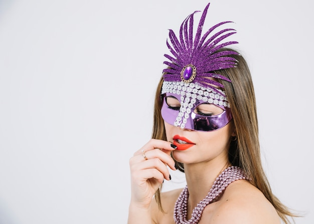 カーニバルマスクとビーズのネックレスを身に着けている美しい女性のクローズアップ 無料写真