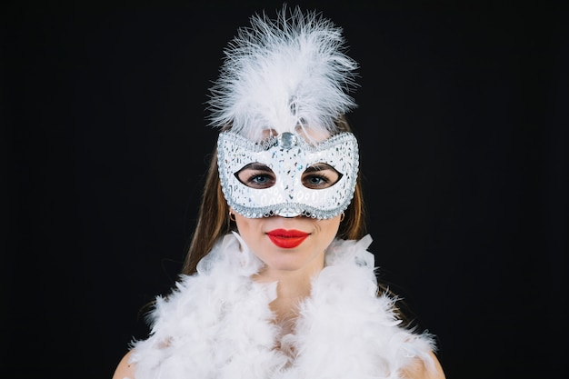 黒の背景にボアの羽を着てカーニバルマスクの女 無料写真